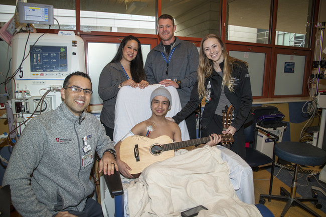 Kayano Lizardo-Bristow, who is awaiting a kidney transplant due to chronic kidney disease, holds his Ed Sheeran-inscribed guitar, surrounded by nurse Colin James, his parents April and Brandon, and music therapist Rebekah Martin at Lucile Packard Children's Hospital Stanford.
