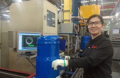 The factory has a clear zero-defects goal and utilizes advanced auto-visual monitoring of compressor parts to check for errors throughout the assembly process. In photo: Line Operator Fenghuan Yan.