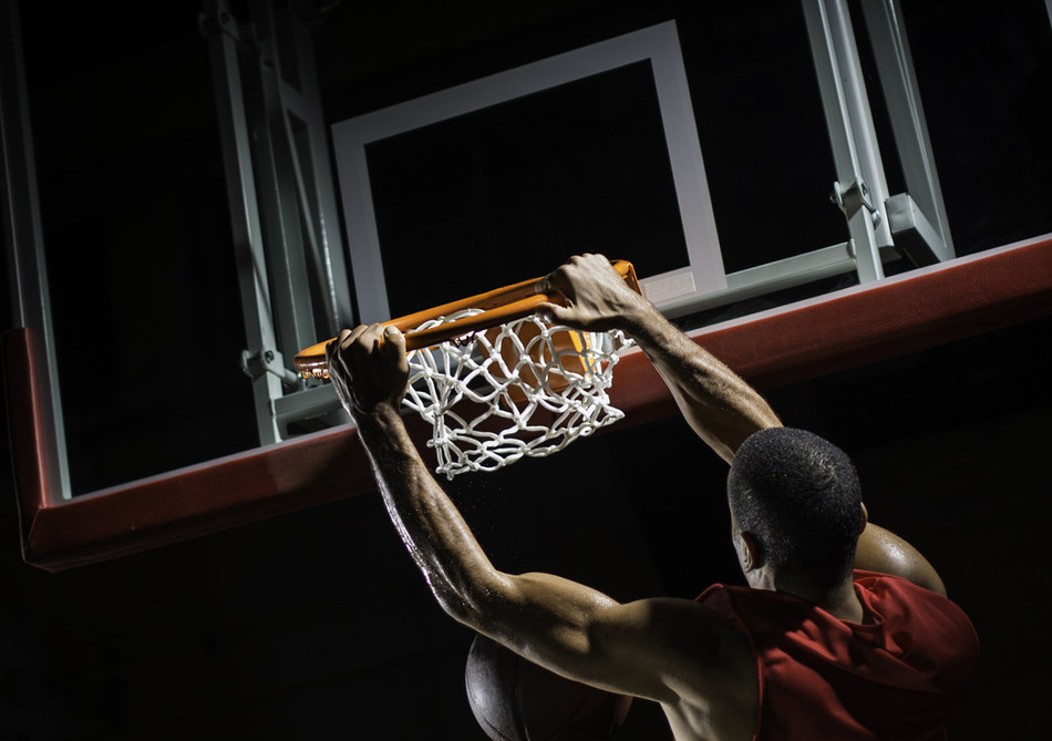 Rear-view shot of a young basketball player in a red jersey in mid-air taking a dunk shot, with both hands clothing the ring.
