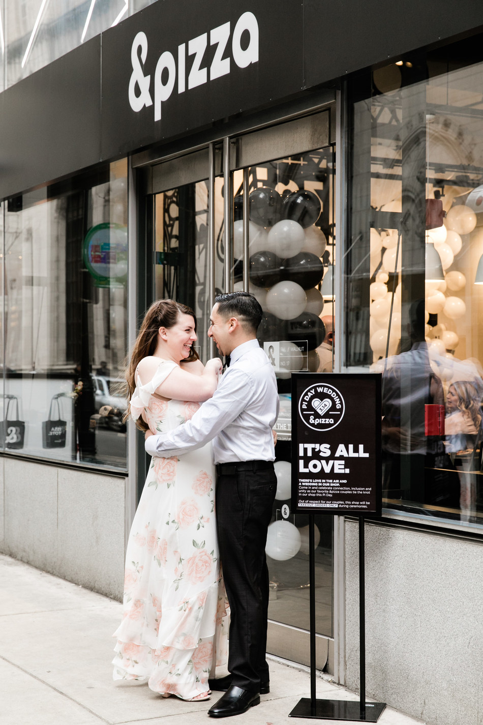 A couple embraces outside of &pizza in Philly after tying the knot in the shop on Pi Day 2018.  The company will again host weddings in select shops on the east coast on Pi Day 2019.