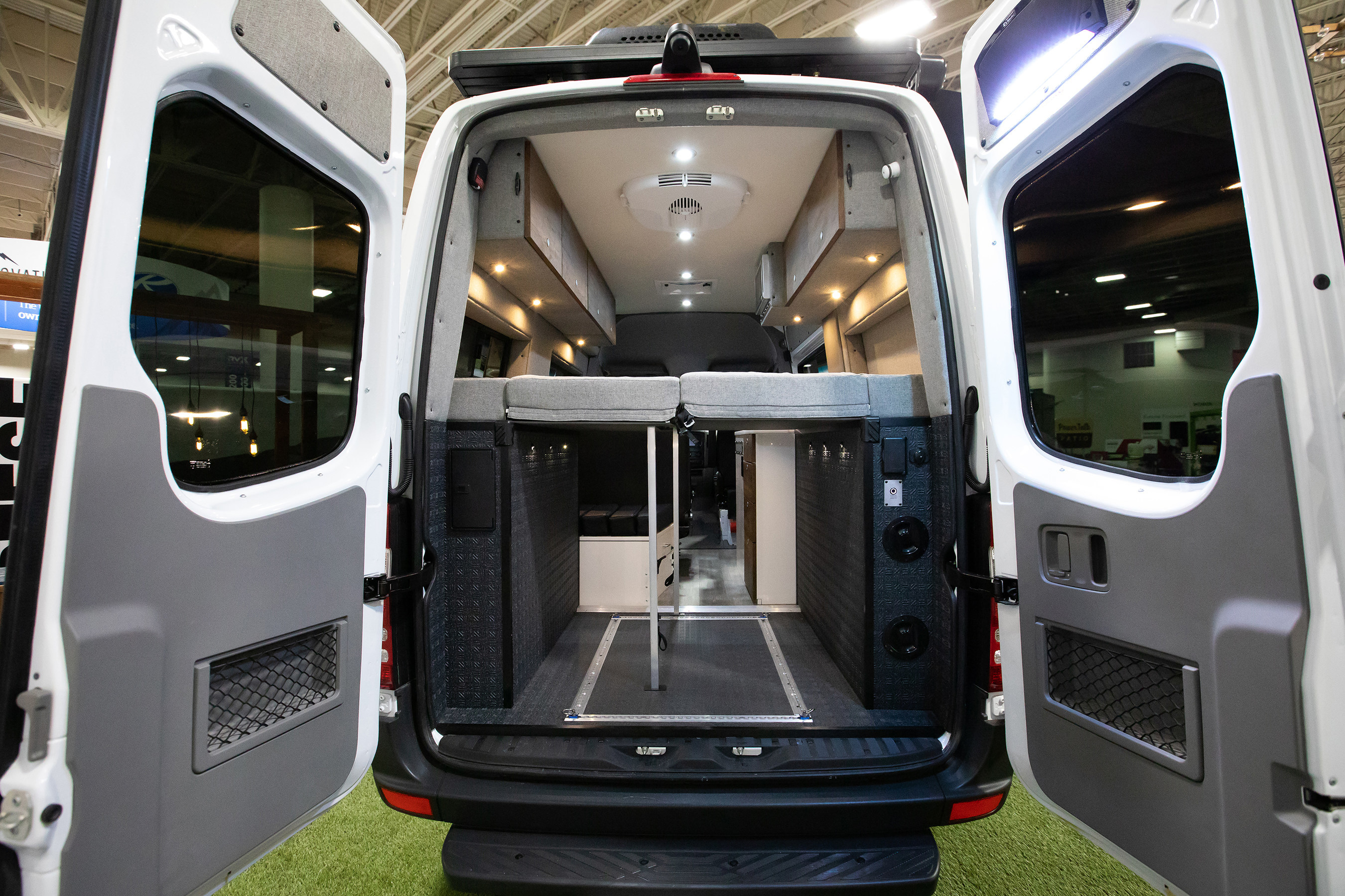 The rear view of the GearHauler garage and the DreamWeaver murphy bed and workbench system in the all new Storyteller Overland MODE 4x4 Adventure Van Series shown here on the Mercedes-Benz Sprinter platform.