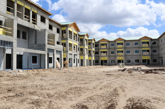 Pictured is the 3-story, under-construction senior living community that will include an outdoor zero-entry pool and cabanas. Discovery Village At Naples - Independent Living is located at 8375 Sierra Meadows Boulevard in Naples, Florida.