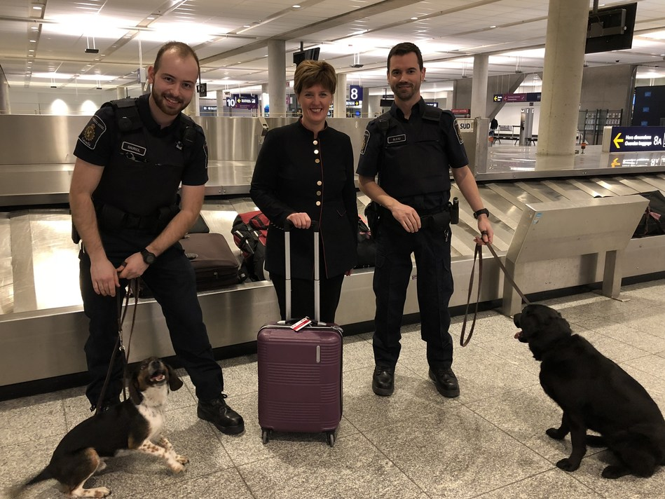 The Honourable Marie-Claude Bibeau, Minister of Agriculture and Agri-Food Canada, stands at the Montréal-Trudeau airport with two Canadian border services officers and two detector dogs (CNW Group/Canadian Food Inspection Agency (CFIA))