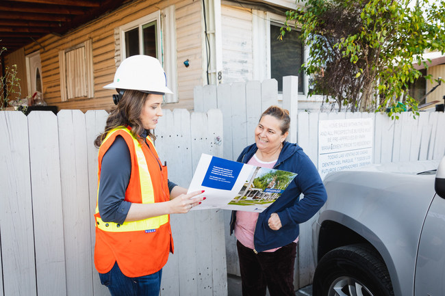 SoCalGas' Karina Esquivel, senior account executive, MHP Utility Upgrade Program, speaking with Maricela Leal, a mobile home park resident at Belmont Mobile Home Park in Compton, California, about the benefits of safe, affordable, natural gas and eligibility for customer assistance programs.