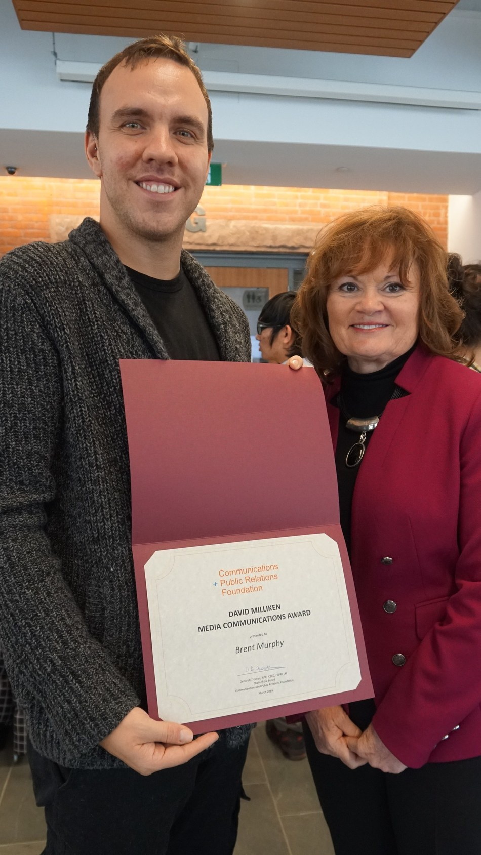Brent Murphy (left) receiving the 2019 David Milliken Media Communications Award from C+PRF Chair Deborah Trouten, APR, FCPRS LM (right). (CNW Group/Communications + Public Relations Foundation)