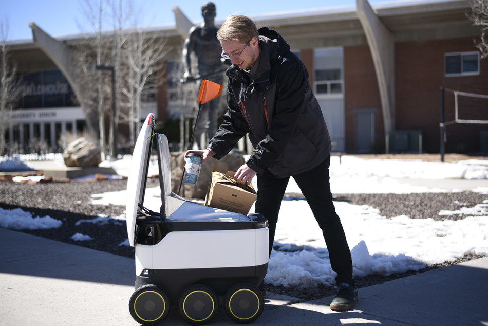 A Starship robot delivers breakfast to a Northern Arizona University student.