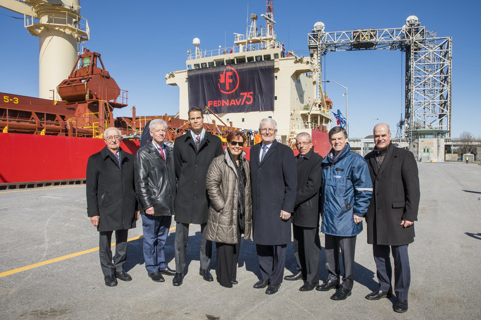 Senior marine industry stakeholders standing in front of the Fednav 75th logo on the Federal Kumano at the Opening ceremony of the St. Lawrence Seaway. (CNW Group/The St. Lawrence Seaway Management Corporation)