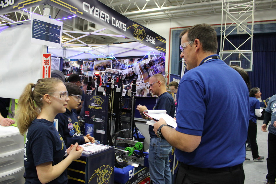 Members of the Cyber Cats Team 5436, based at Stoney Creek High School in Rochester, Michigan, discuss their 'bot' with the judges at a recent FIRST Robotics Competition. DENSO is one of the team's sponsors and provides the Cyber Cats with monetary support and mentoring.