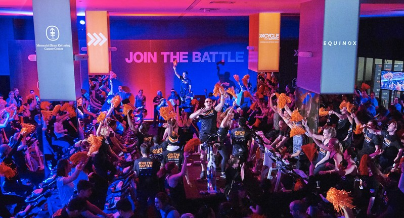 Rare cancer survivors, patients, caregivers, doctors and supporters ride at a Cycle for Survival event. The indoor team cycling events are led by instructors from Equinox, Cycle for Survival's founding partner, in 16 cities across the country. Cycle for Survival is celebrating $42 million raised in 2019.
