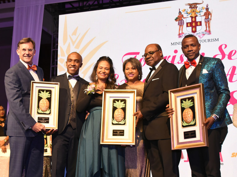 Jamaica's Minister of Tourism, Edmund Bartlett (second right) presents the National Champion organization award to Half Moon, represented by (L-R) Chairman, Guy Steuart III; Brand and Communications Director, Laura Redpath; Interim General Manager, Shernette Crichton and Training Manager, Conroy Thompson at the Tourism Service Excellence Awards. Also pictured is Dr. Andrew Spencer, Executive Director of the Tourism Product Development Company (TPDCO).