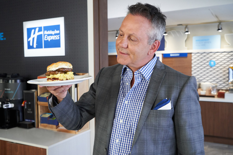 "Doug Gilmour with ""The Gloves Off Breakfast Sandwich,"" a biscuit topped with strawberry jam, a sausage patty, scrambled eggs and cream cheese. (CNW Group/Holiday Inn Express)"