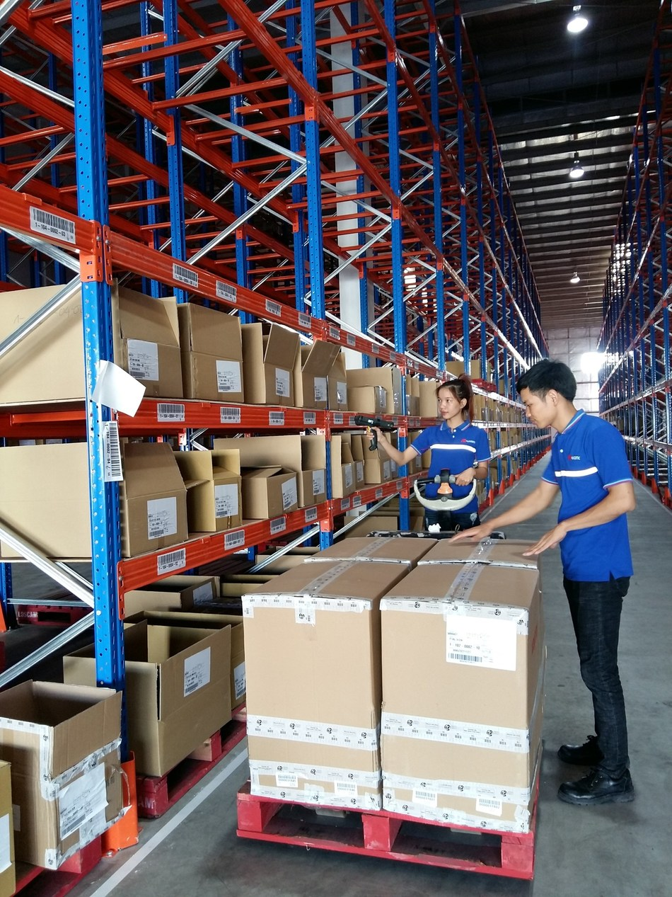 Warehouse operators scan packages at FM Logistic warehouse and DC