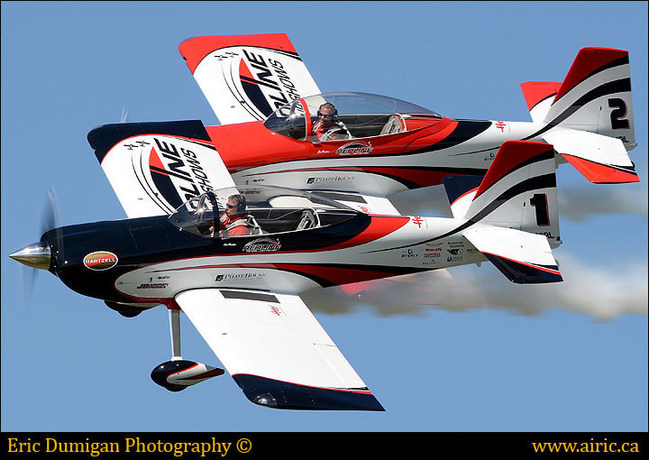 The twin Vans RV-8 aircraft fly in a tight-formation during an air show demonstration.