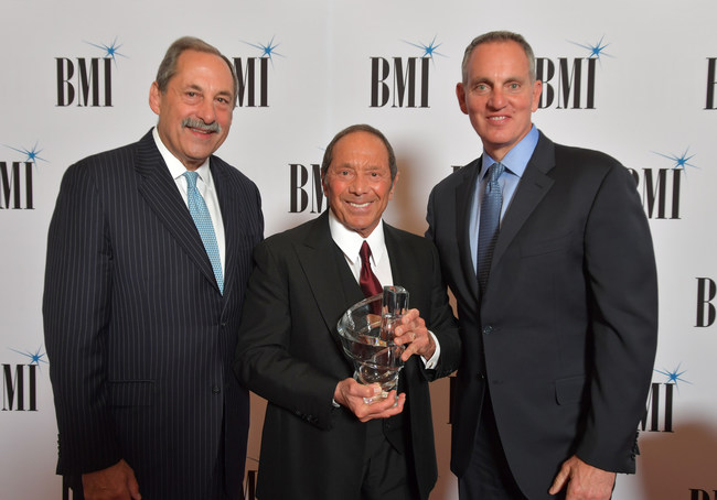Michael Fiorile, Chairman, BMI Board of Directors & Chairman and CEO, The Dispatch Printing Company and BMI President and CEO Mike O'Neill present Paul Anka with the BMI Board of Directors Award at the 71st Annual BMI/NAB Dinner. Photo: Lester Cohen for BMI.