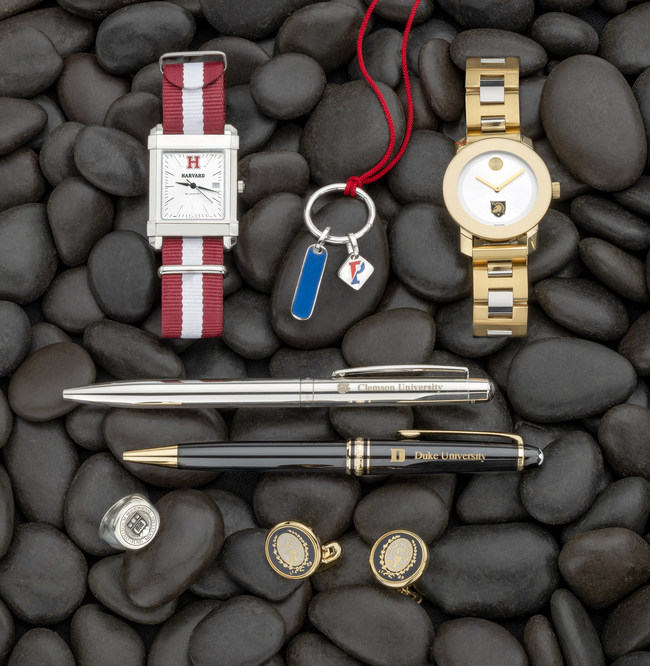 Some examples from the M.LaHart Top 10 Graduation Gifts List include wrist watch with school name and initials, luxury writing pen with school name, school ring with personalized engraving, cuff links customized with school crest, and necklace with school pendant.
