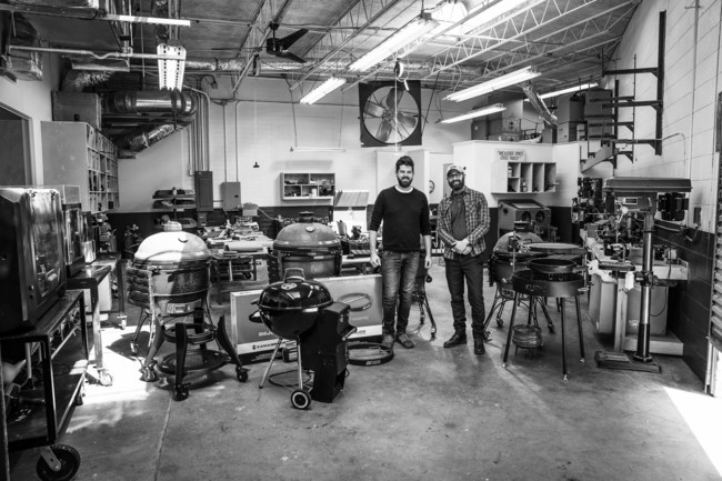 Joseph Pruitt, CEO and Founder of Atlas Product Manufacturing Group, and Jeff Broadrick, Senior Project Engineer, stand in their shop with a selection of the grills and accessories they have helped create.