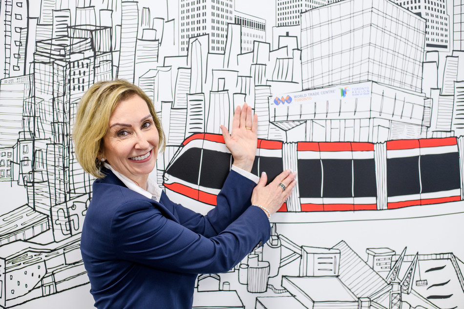 Jan De Silva, President & CEO, Toronto Region Board of Trade showcasing the World Trade Centre Toronto and the Toronto Region Board of Trade's new home at 100 Queens Quay East on a mural in their current office. (CNW Group/Menkes Developments Ltd)