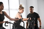 A personal trainer encourages two people during a Life Time group fitness class