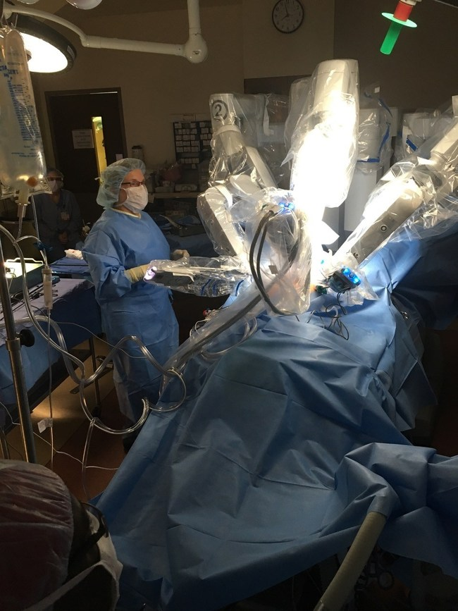 Surgeon and OR team performing robotic surgery.