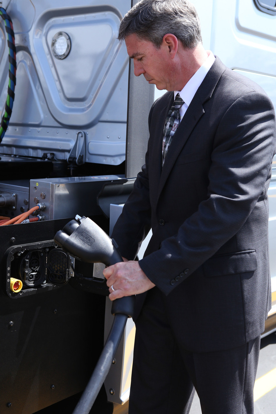 Andrew Cullen, senior vice president of fuels and facilities at Penske Truck Leasing preparing to charge Daimler Trucks North America's electric class 8 Freightliner eCascadia semi-truck.