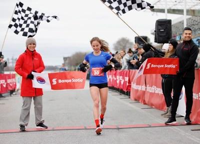 Québec's Anne-Marie Comeau crosses the finish line first in the women's event at the Banque Scotia 21k de Montréal race. (CNW Group/Scotiabank)