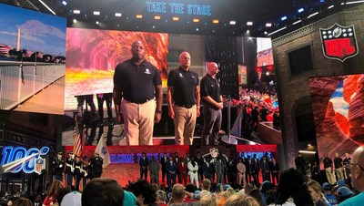 Three warriors stand on stage during the national anthem at the 2019 NFL Draft in Nashville, Tennessee.