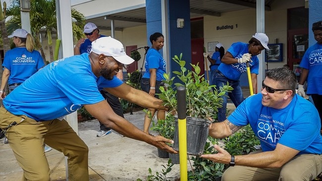 During the 2019 Comcast Cares Day at Forest Hill Elementary School in West Palm Beach, Assistant Principal Sean Higgins works with Principal Scott McNichols to plant new shrubs.