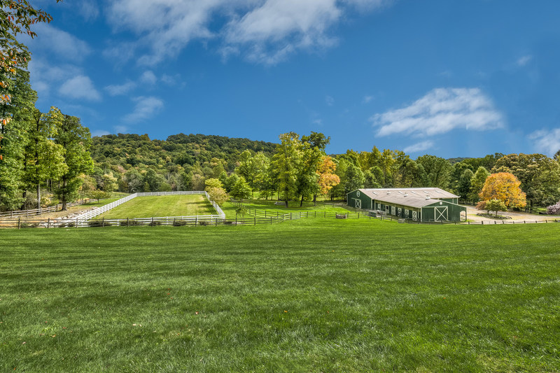 The farm's 8-stall barn include a 60-ft by 120-ft indoor arena, tack room and storage areas. The grounds also contain multiple paddocks, an outdoor riding ring, split-rail fencing and miles of trails. LigonierLuxuryAuction.com.
