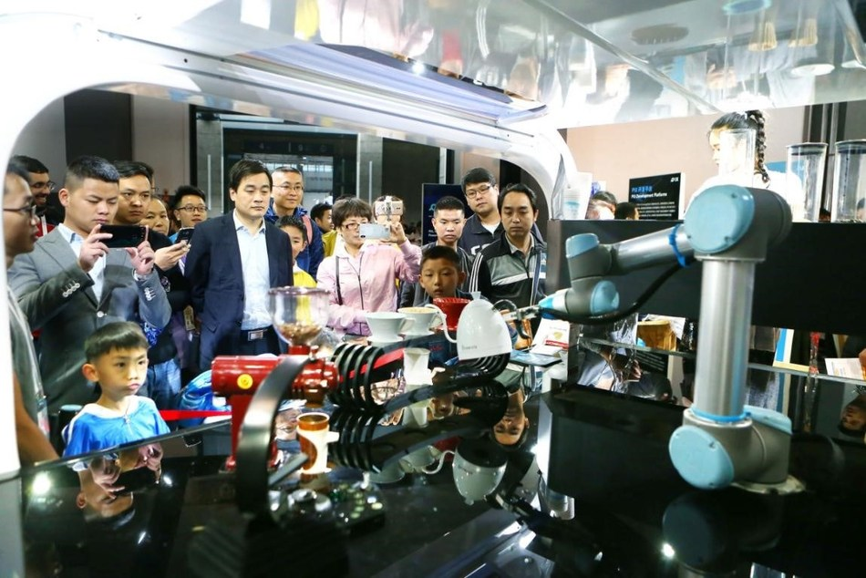 Visitors look at a coffee brewing robot during the 2018 China International Big Data Industry Expo in Guiyang city, southwest China's Guizhou province.