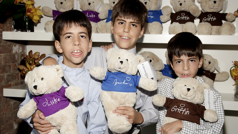 Luke Lori, Zack Lori and Griffin Lori holding the Three Little Bears that are given to children during Operation Smile medical missions.