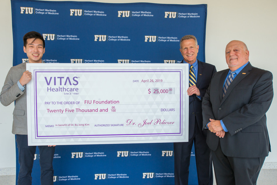 FIU graduate and VITAS Healthcare 2019 Scholar, Dr. Bu Jung Kim (left) is presented with a $25,000 check by Dean of HWCOM Dr. Robert Sackstein (center) and Dr. Joel S. Policzer.