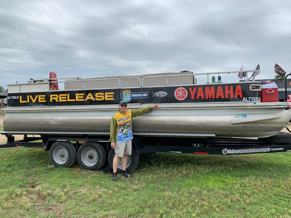 B.A.S.S. Conservation Director Gene Gilliland shows off one of four Yamaha-sponsored live-release boats used in Bassmaster tournaments.