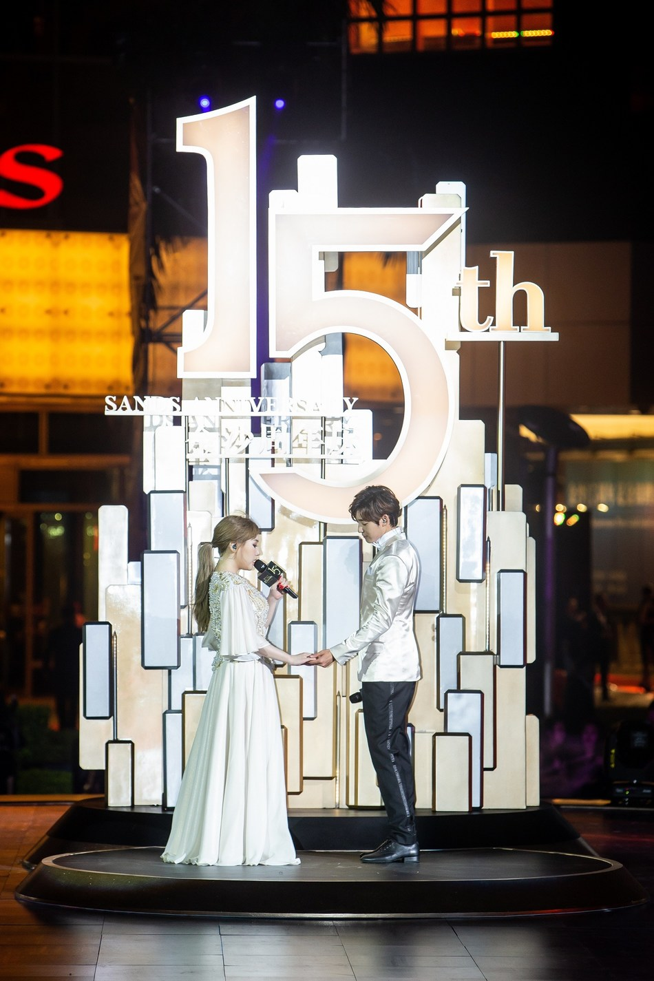 """A waterfall-styled pyrotechnic display in front of Sands Macao's façade Thursday illuminates the night in front of the hotel and entertainment complex's outdoor fountain in celebration of the property's 15th anniversary, while Korean singers Kevin Woo and Jimin Park sing """"Rewrite the Stars"""" from the Grammy-Award-winning soundtrack from the film """"The Greatest Showman."""""""