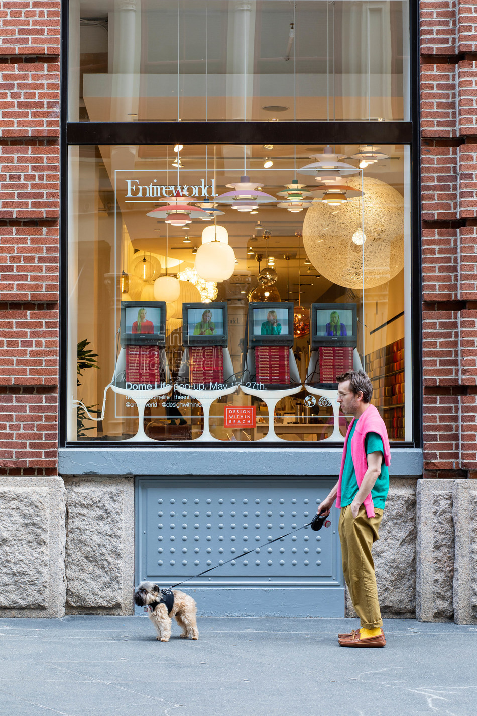 Entireworld Founder and Creative Director Scott Sternberg stands with his dog General Zod in front of the Dome Life pop-up at DWR's SoHo Studio. In the windows, original video created by Entireworld brings the concept to life – models wearing Entireworld interact with furniture and objects from Design Within Reach. Photo: Alexander Kusak