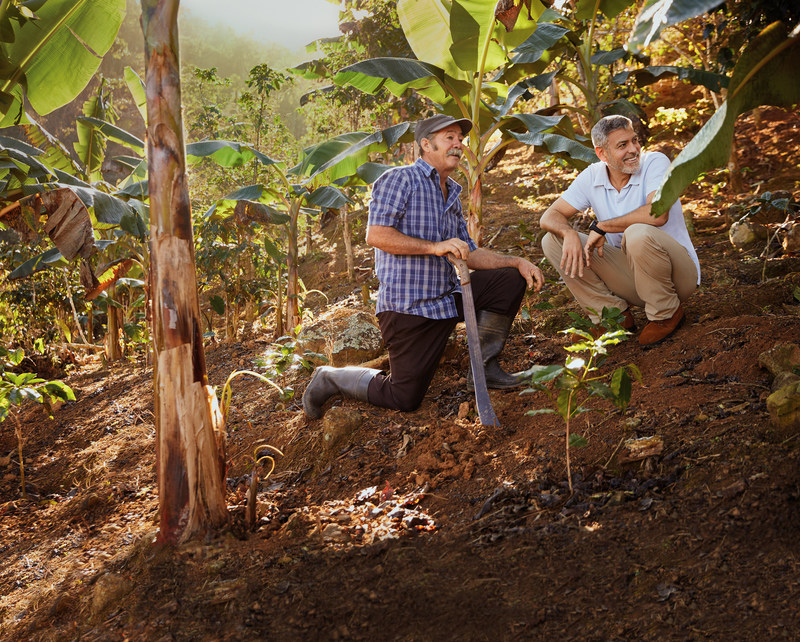 George Clooney surveys the land on José Arroyo's coffee farm in Adjuntas, Puerto Rico, as part of the Nespresso Reviving Origins program. The initiative works with farmers to help rebuild high-quality coffee production that has been threatened by natural disaster or conflict.