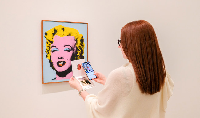 A visitor to Levy Gorvy's Warhol Women scans an NFC tag in the gallery's collateral, activating an immersive digital experience on her phone that complements physical exhibition.