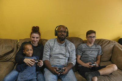 Wounded warrior James Martin (center) plays a video game with his family. Your livestream can help support critical physical and mental health programs warriors like James use in their transitions to civilian life.