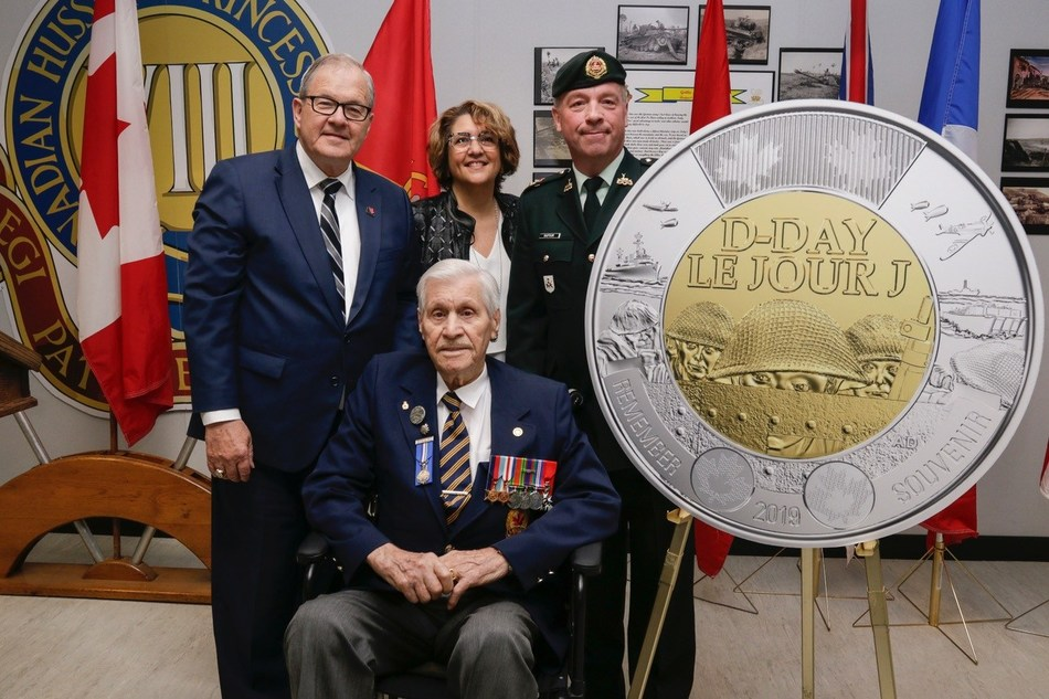 The unveiling of the $2 circulation coin commemorating the 75th anniversary of D-Day at the Moncton Garrison (May 27, 2019).  From left: Veterans Affairs Minister Lawrence MacAulay, Royal Canadian Mint CEO Marie Lemay, North Shore Regiment Commander LCol Rénald Dufour and D-Day veteran Alphonse Vautour (seated). (CNW Group/Royal Canadian Mint)