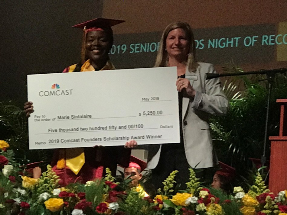 Marie Sintulaire of Belle Glade, Glades Central Community High School, receiving her Comcast Founders Scholarship check from Carla Roderick, Director of External Affairs and Community Impact for Comcast in Palm Beach County and the Treasure Coast.