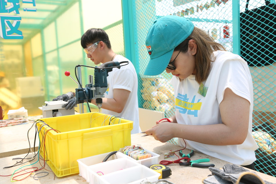 Volunteers with Meituan's Blue Mountain Project make gadgets from recycled food packaging materials during an event in Beijing last month.