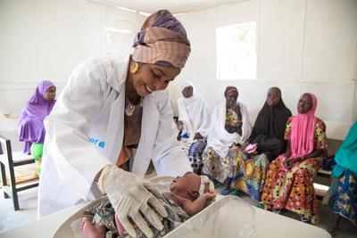 Une sage-femme soutenue par l'UNICEF mesure la tête d'un nouveau-né dans une clinique soutenue par l'UNICEF dans le camp pour personnes déplacées de Muna Garaga, à Maiduguri, dans l'état de Borno au Nigéria. © UNICEF/UN0158794/Naftalin (Groupe CNW/UNICEF Canada)