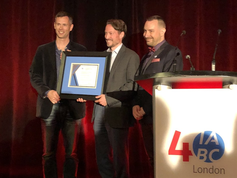 Dr. Christopher Mackie (centre) is presented the 2019 IABC London Outstanding Communicator Award at the chapter's 40th anniversary celebration on June 6. Presenting the award are 2017 Outstanding Communicator Award winner Andrew McLenaghan (left) and IABC London chapter president Andrew Kaszowski (right). (CNW Group/IABC London)