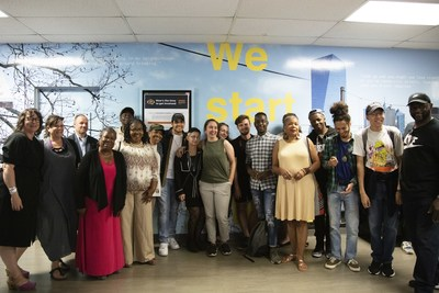 TRIPOD at Writers Room community and student participants pose for a photo in front of mural printed on the Océ Colorado 1640 and installed in front of Drexel University's English Department.