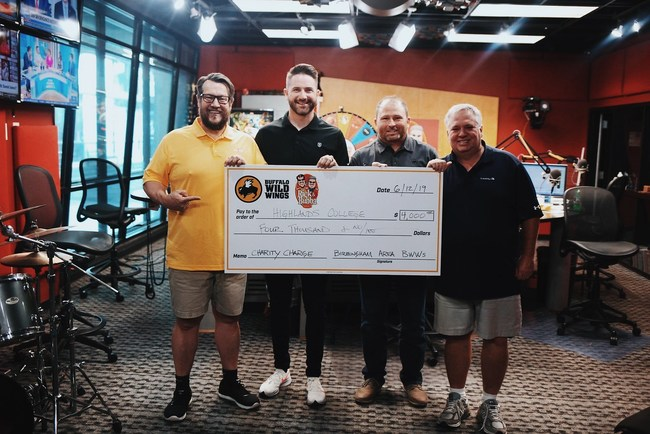 Pastor Mark Pettus stands with hosts Rick Burgess and Bubba Bussey as Buffalo Wild Wings representative Tim Spencer presents Highlands College a $4,000 check.