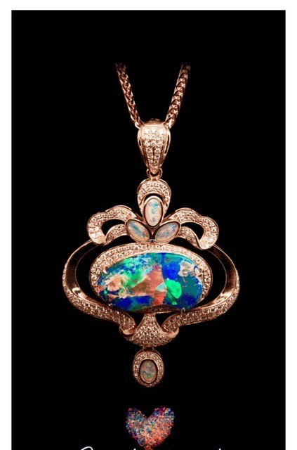 An 18-karat rose gold pendant with boulder opal centre stones and diamond accents by Regent Opal