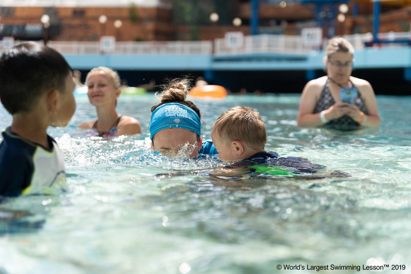 "A swim instructor at World Waterpark, West Edmonton, Canada, helps a young swimmer practice how to blow bubbles and breathe during the World's Largest Swimming Lesson.  The 24-hour global event spreads the message ""Swimming Lessons Save Lives"" to families in 30 different countries to help prevent drowning. The World Health Organization (WHO) estimates drowning is the 3rd leading cause of unintentional injury death worldwide, accounting for 7% of all injury-related deaths."