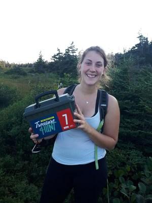 Sarah Pitcher découvre un coffre lors de la chasse au trésor du Grand Sentier de 2018 sur le sentier de la côte Est de Terre-Neuve. (Groupe CNW/Société géographique royale du Canada)