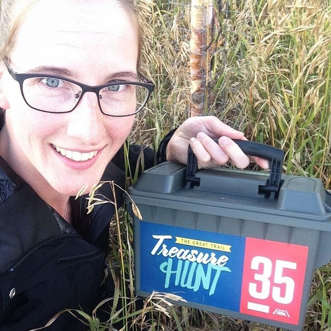 Gina Van Haren finds box 35 on the Trail in Airdrie, Alberta while on the Great Trail Treasure Hunt in 2018 (CNW Group/Royal Canadian Geographical Society)