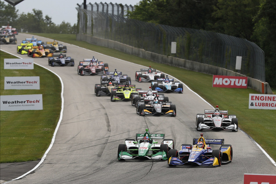 Driving the #27 Andretti Autosport Honda (right), Alexander Rossi sweeps across the front of pole qualifier and fellow Honda driver Colton Herta to take the lead in today's REV Group Grand Prix at Road America.  Rossi went on to dominate today's NTT IndyCar Series race for his second win of the season, and the fifth for a Honda driver.