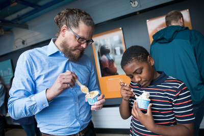 Ben & Jerry's CEO Matthew McCarthy and Rasir Corzen, 11, of Philadelphia, Pa., enjoy ice cream while viewing the newly opened Art for Justice exhibit at the Ben & Jerry's factory on Tuesday, June 25, 2019 in Waterbury, Vt. The exhibit highlights the need for criminal justice reform and features artwork by formerly-incarcerated artists. (Andy Duback/AP Images for Ben & Jerry's)